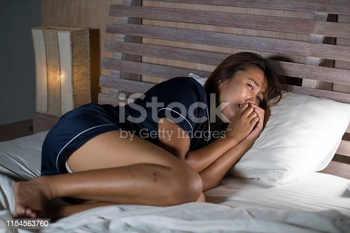 867034754istockphoto dramatic lifestyle portrait of young attractive sad and depressed Asian woman in pajamas lying in bed in pain suffering depression and anxiety feeling lonely and desperate after break up relationship 1154563760