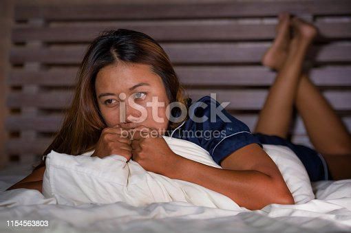 867034754istockphoto dramatic lifestyle portrait of young attractive sad and depressed Asian woman in pajamas lying in bed in pain suffering depression and anxiety feeling lonely and desperate after break up relationship 1154563803