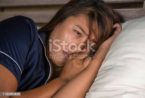 867034754istockphoto dramatic lifestyle portrait of young attractive sad and depressed Asian woman in pajamas lying in bed in pain suffering depression and anxiety feeling lonely and desperate after break up relationship 1154563835