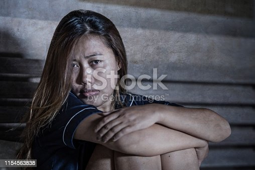 867034754istockphoto dramatic lifestyle portrait of young attractive sad and depressed Asian woman in pajamas lying in bed in pain suffering depression and anxiety feeling lonely and desperate after break up relationship 1154563838