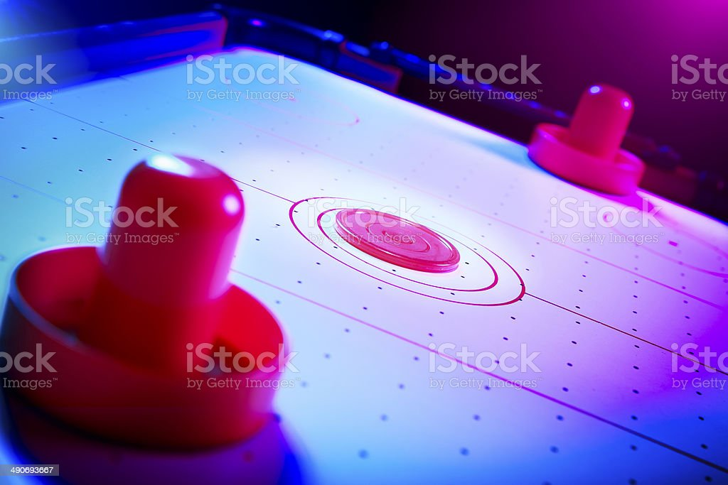 Dramatic lit air hockey table with puck and paddles stock photo