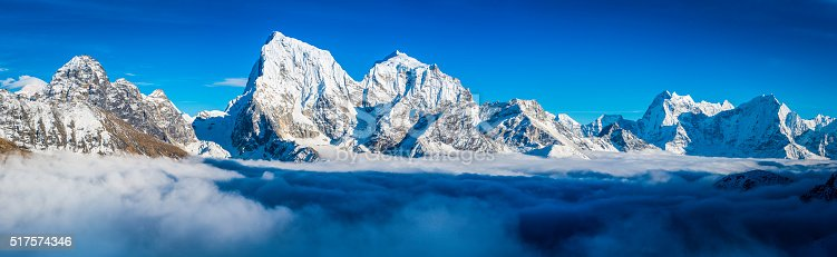 Deep blue high altitude skies above the snowy summits of Cholatse (6440m), Taboche (6542m), Kangtega (6752m) and Thamserku (6623m) rising through the clouds covering the Ngozumpa glacier and Gokyo deep in the remote Himalayan mountain wilderness of the Everest National Park on the Nepal Tibet border, a UNESCO World Heritage Site. ProPhoto RGB profile for maximum color fidelity and gamut.