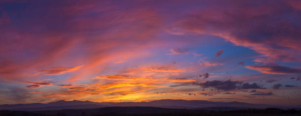 Dramatic Mountain Sunset Panorama Wide high view of a mountain sunset with dramatic sky panorama. twilight stock pictures, royalty-free photos & images