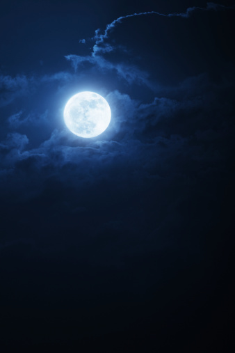 This dramatic photo illustration of a nighttime scene with brightly lit clouds and large, full, Blue Moon would make a great background for many uses.