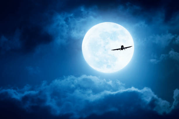 Dramatic Nighttime Sky With Large Full Blue Moon and Commercial Aircraft stock photo