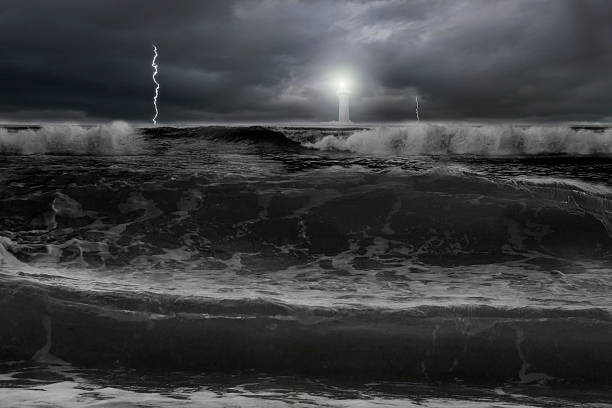 Dramatic ocean, dark cloudy sky with lightning lighthouse in front stock photo
