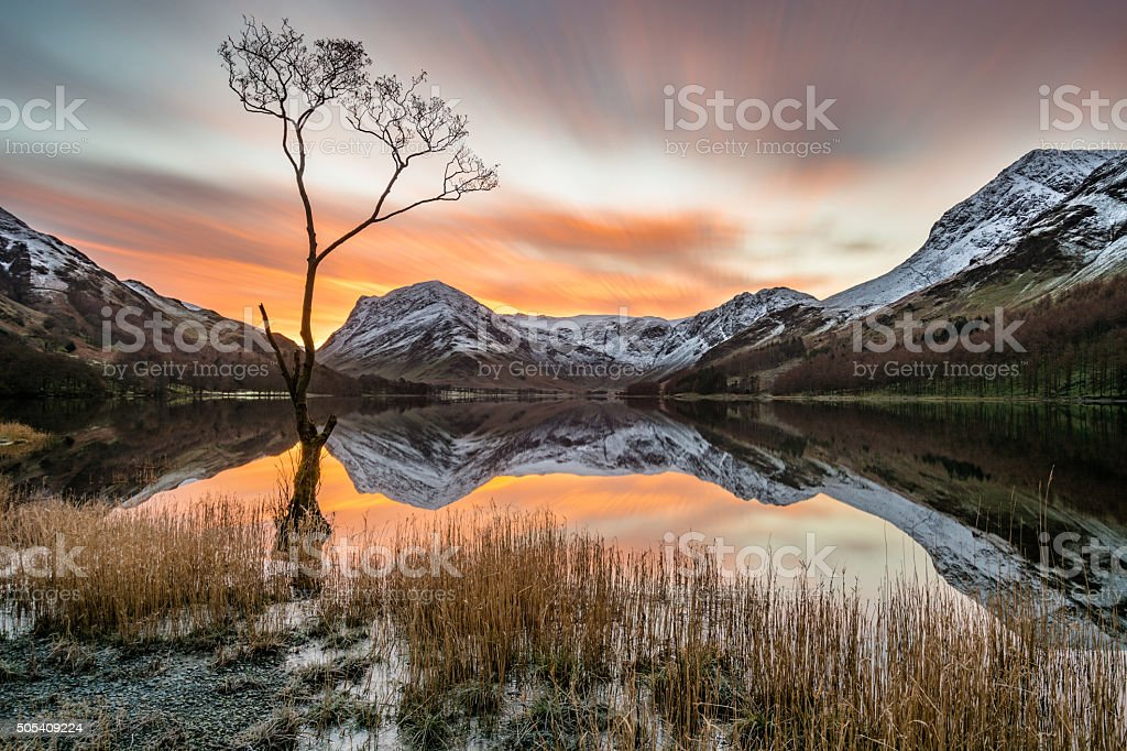 Dramatic Orange Sunrise Over Snow Covered Mountains With Reflections. stock photo