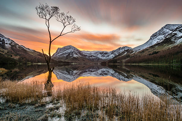 dramatische orange sonnenaufgang über schneebedeckte berge mit reflexionen. - cumbria stock-fotos und bilder