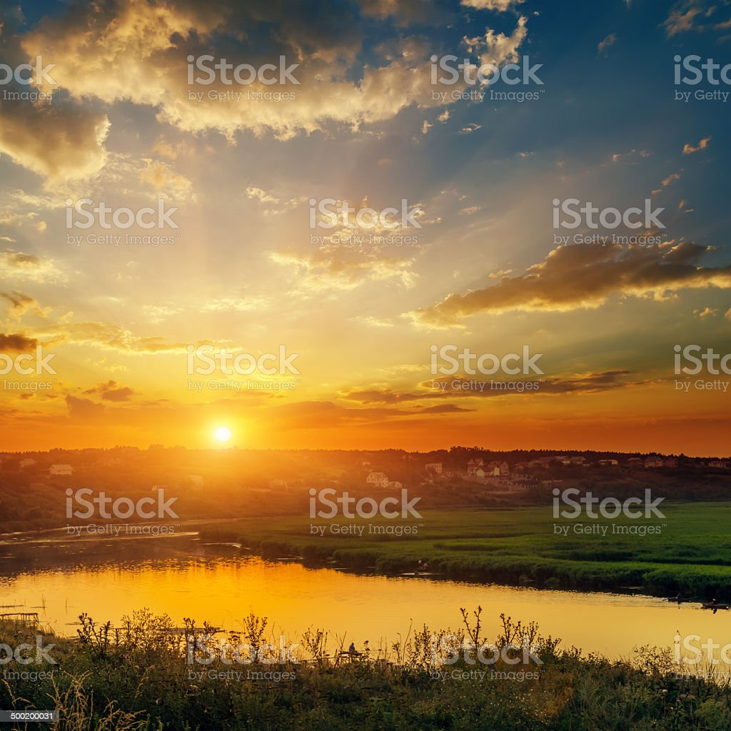 dramatic orange sunset over river stock photo