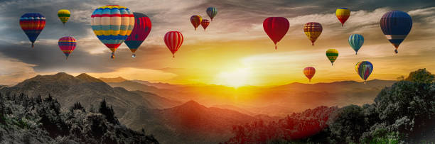 Dramatic panorama of mountain with hot air balloons at sunset,Thailand. stock photo