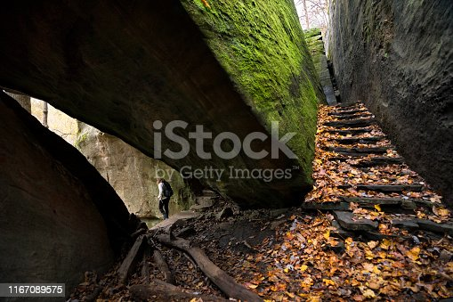Solo hiker descends leaf covered stone steps and passes through a narrow opening between giant mossy rocks at  Pounds Hollow on an Autumn day, near Garden of the Gods, Illinois, USA