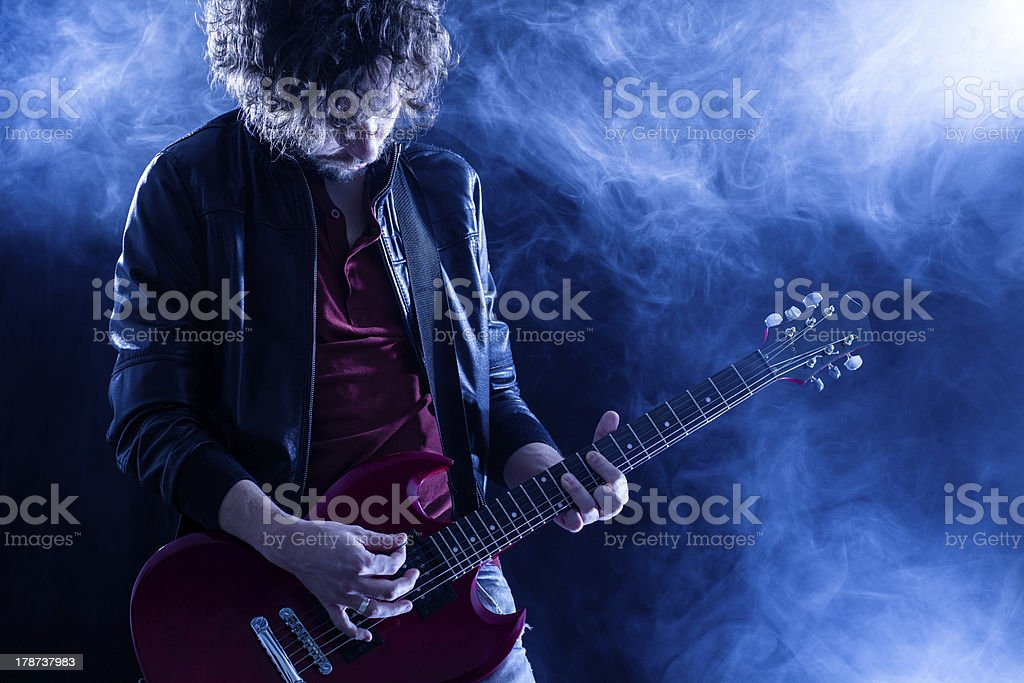 Dramatic photo of rock guitarist surrounded by smoke stock photo