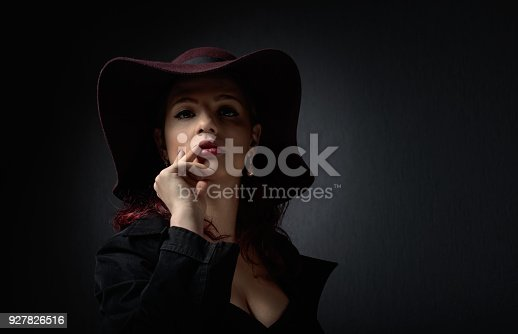 Dramatic portrait of a beautiful woman in hat with perfect hair and makeup . Studio shot . Copy space .