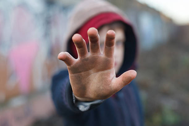 dramatic portrait of a little homeless boy, dirty hand stock photo