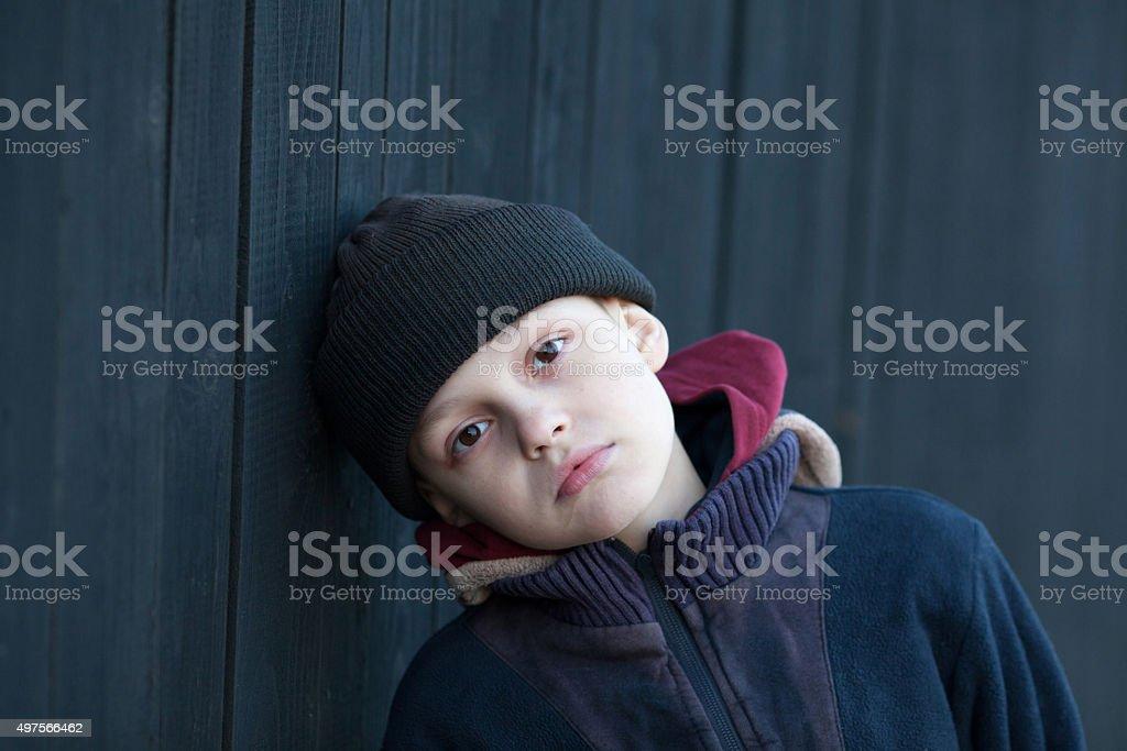 dramatic portrait of a little homeless boy stock photo