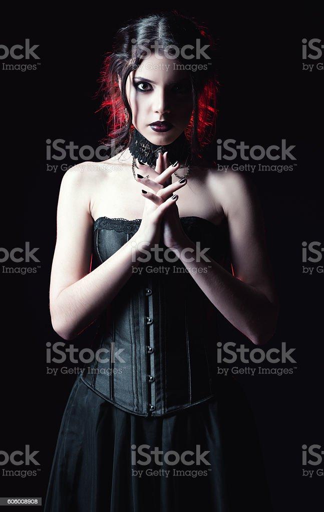 Dramatic portrait of beautiful goth woman among the dark stock photo
