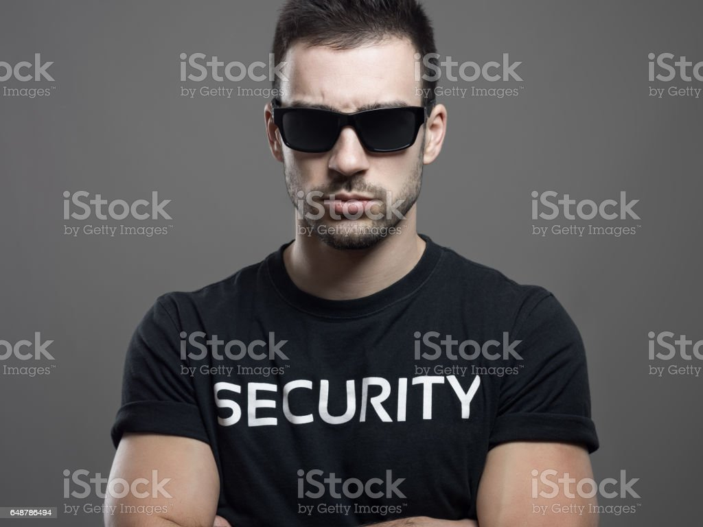 Dramatic portrait of tough security guard man with crossed arms stock photo