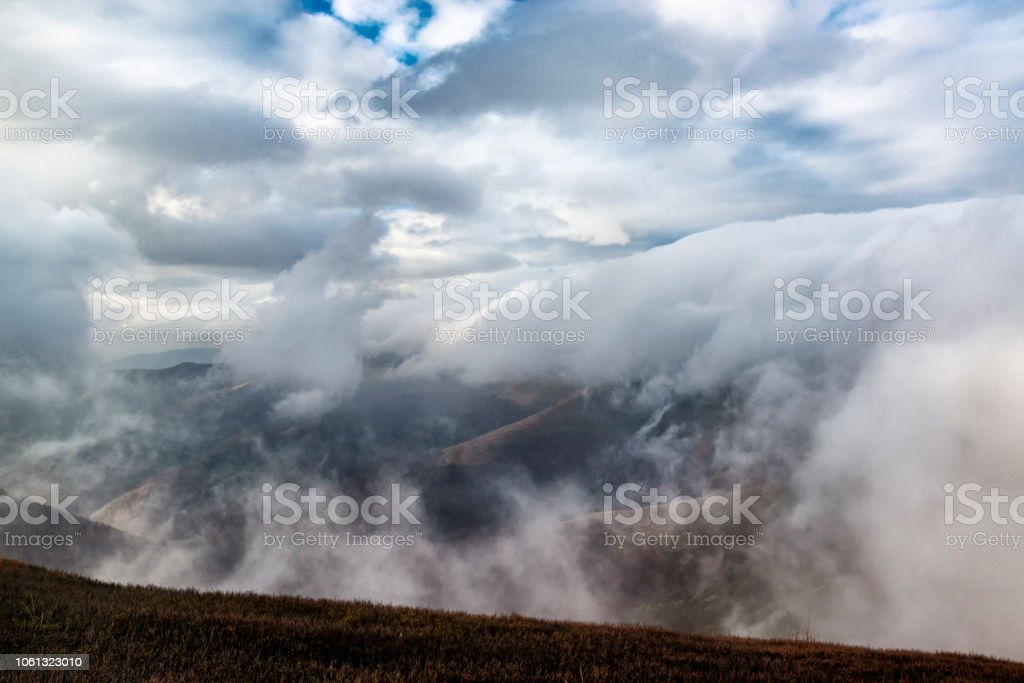 Dramatic rainy alpine landscape with rain clouds below the mountain....