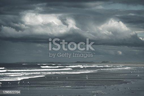 Dramatic rainy cloudy sky over dark empty beach
