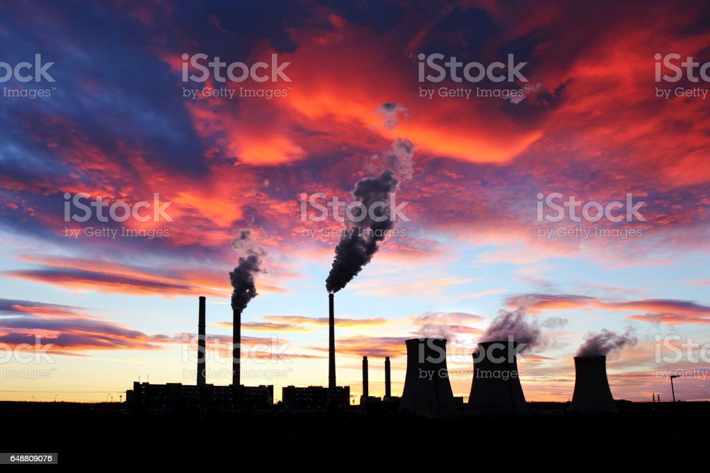 dramatic red sunset over brown coal power station stock photo