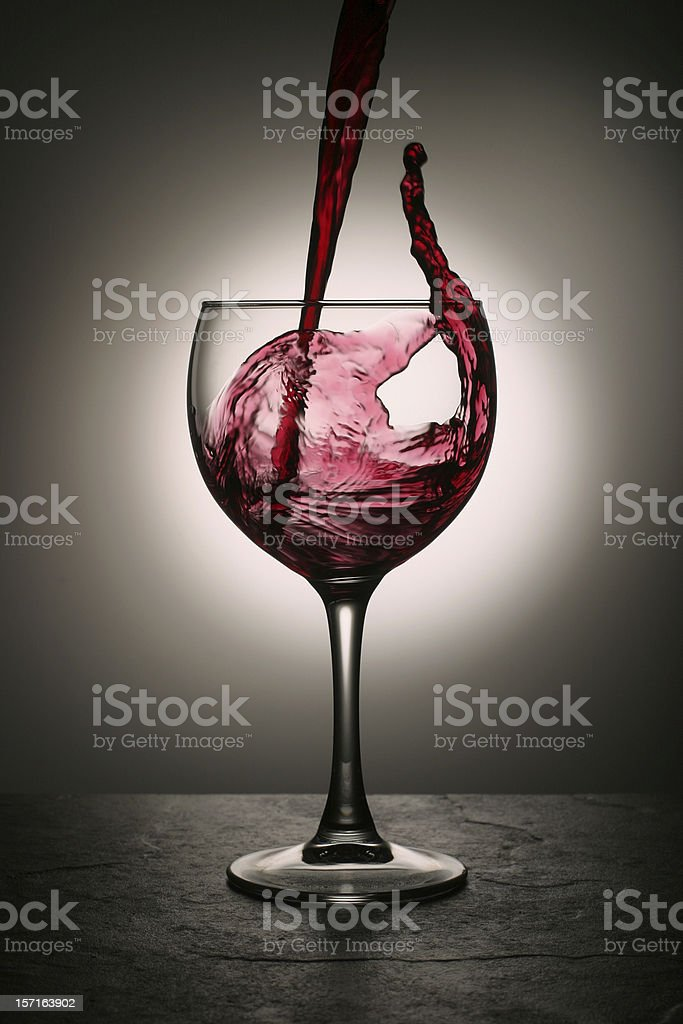 Dramatic Red Wine Splash into Wine Glass royalty-free stock photo