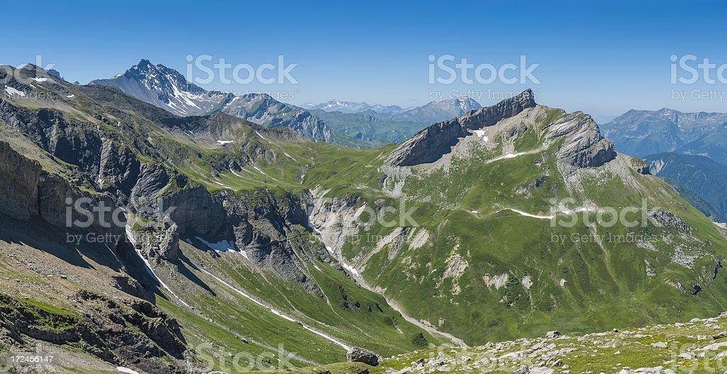 Dramatic rocky peaks green summer alpine meadows panorama royalty-free stock photo