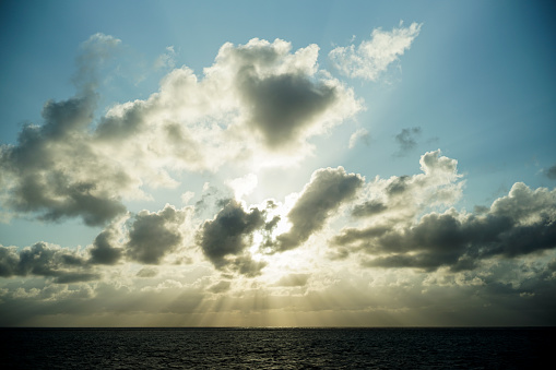 Dramatic scenery of backlit sky and sea in the evening at Miyako Island.\nThe sun shines brightly through the gaps in the clouds, and a radial line of light pours into the sea.\nPowerful sunshine, an impressive view.\nLight from heaven.