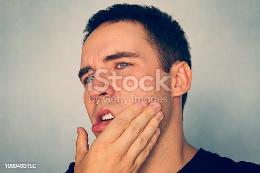 istock Dramatic Shot of a Man in Pain holding his Jaw. Toothache. A punch in the jaw Slap. Insult. The guy strokes his chin after shaving. stomatitis, periodontal disease, tooth extraction. 1000493152