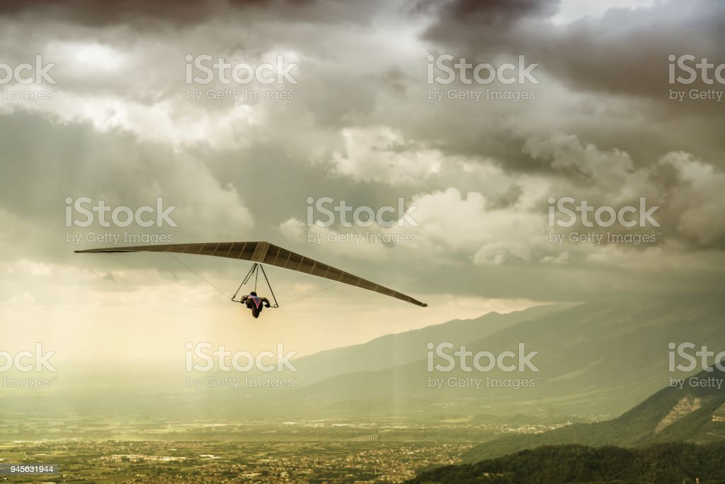 Dramatic shot of brave extreme hangglider pilot flying his wing in a stormy weather with big rain thunderstorm clouds. stock photo