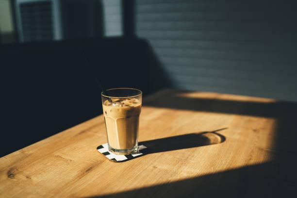 dramatische schuss von eiskaffee bei sonnenuntergang mit schatten - hausgemachter eiskaffee stock-fotos und bilder