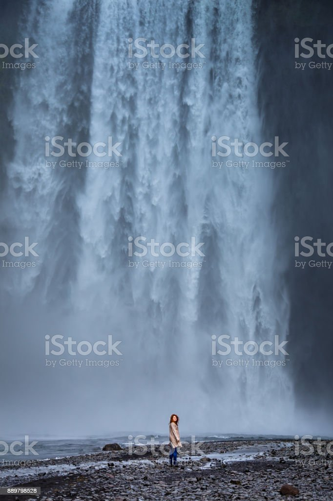 Dramatic Shot of Lone Woman at the Foot of Skógafoss, Iceland stock photo