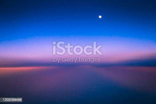 1045890176 istock photo Dramatic Sky above clouds and full moon from airplane window – Usa, North America 1203269459