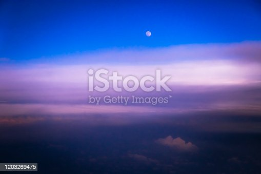 1045890176 istock photo Dramatic Sky above clouds and full moon from airplane window – Usa, North America 1203269475