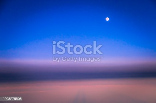 1045890176 istock photo Dramatic Sky above clouds and full moon from airplane window – Usa, North America 1203275508