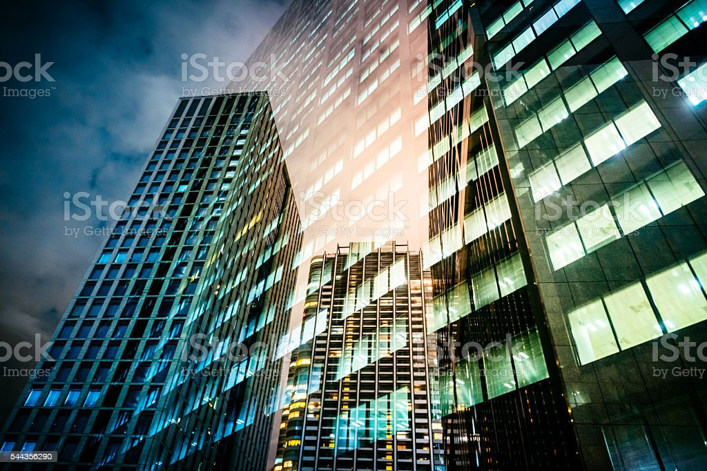 Dramatic sky and corporate architecture reflecting at night in glass stock photo