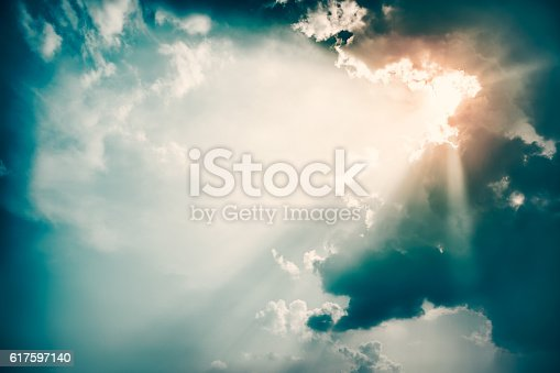 Dramatic Sky and Sun Rays Background. Stormy Clouds in Dark Sky. Sunbeams Light and Moody Cloudscape. Toned and Filtered Photo with Copy Space.