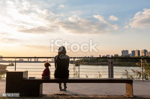 rear view of woman with her pet poodle sitting on park bench viewing beautiful sunset scenery.