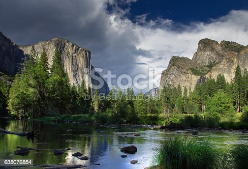 A thick sheet of gray cloud rolling over the granite formations of El Capitan and the Three Brothers, seen from the  floor of Yosemite Valley on the banks of the Merced River. Still taken from time lapse video #610816938.
