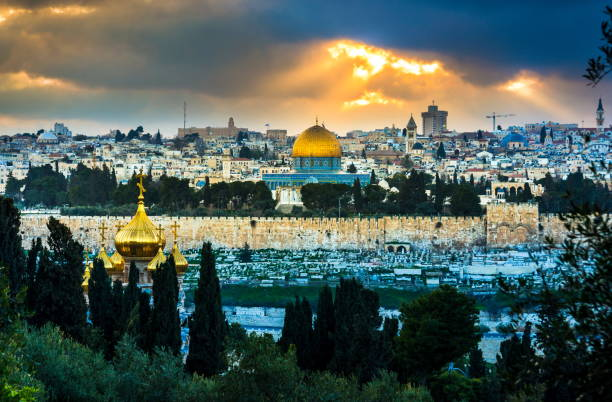 Dramatic sky over Jerusalem Sun rays breaking through dark clouds over Jerusalerm and the Mount of Olives dome of the rock stock pictures, royalty-free photos & images