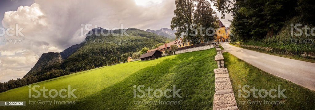 Dramatic Sky Over Lush Green Mountain and Landscape in the Alps stock photo