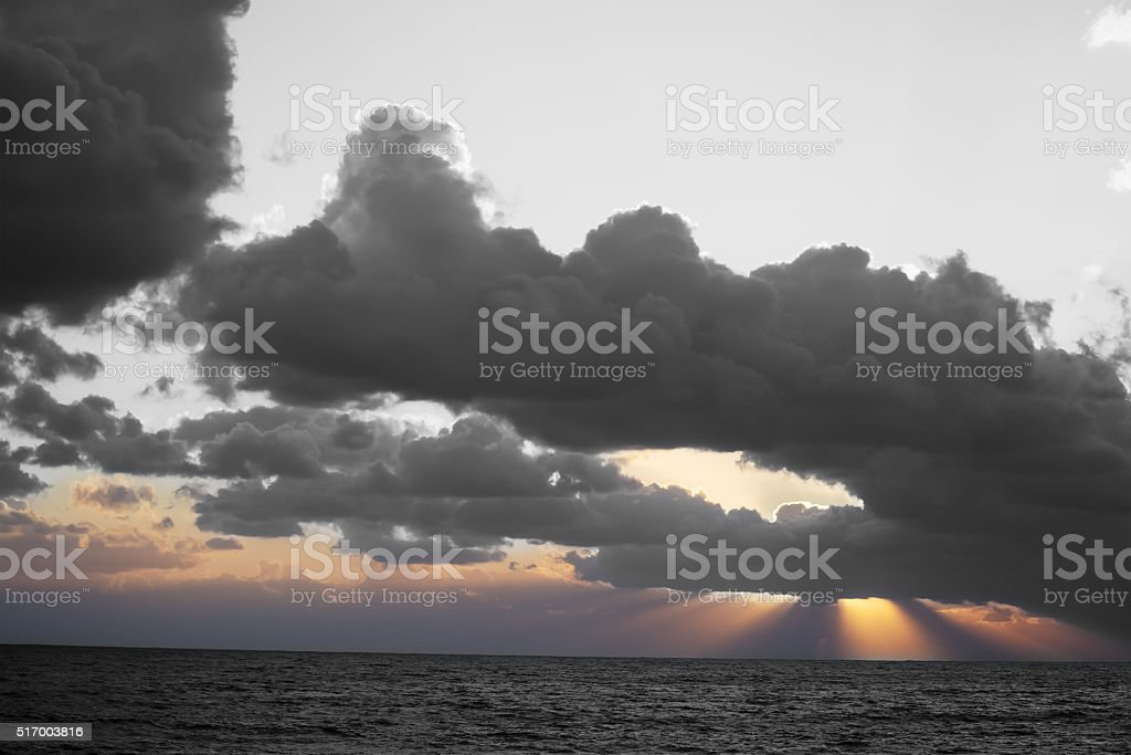 dramatic sky over the sea at sunset stock photo