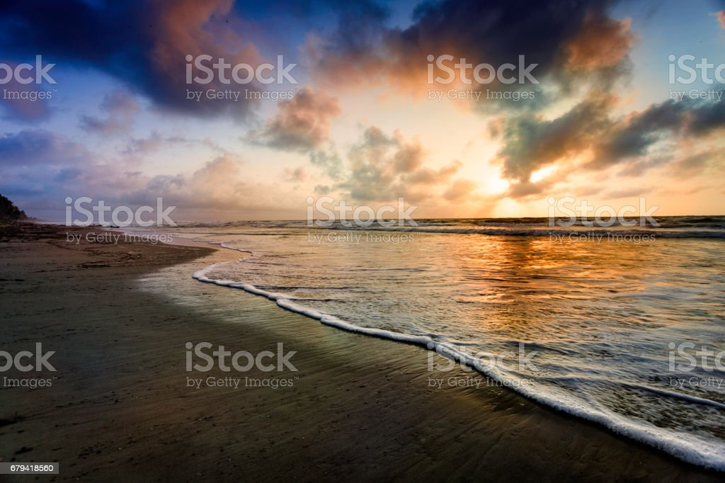 Dramatic sky reflection on a tropical beach at sunrise stock photo