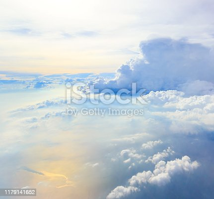 White clouds and blue sky over blue ocean as seen through window of an aircraft