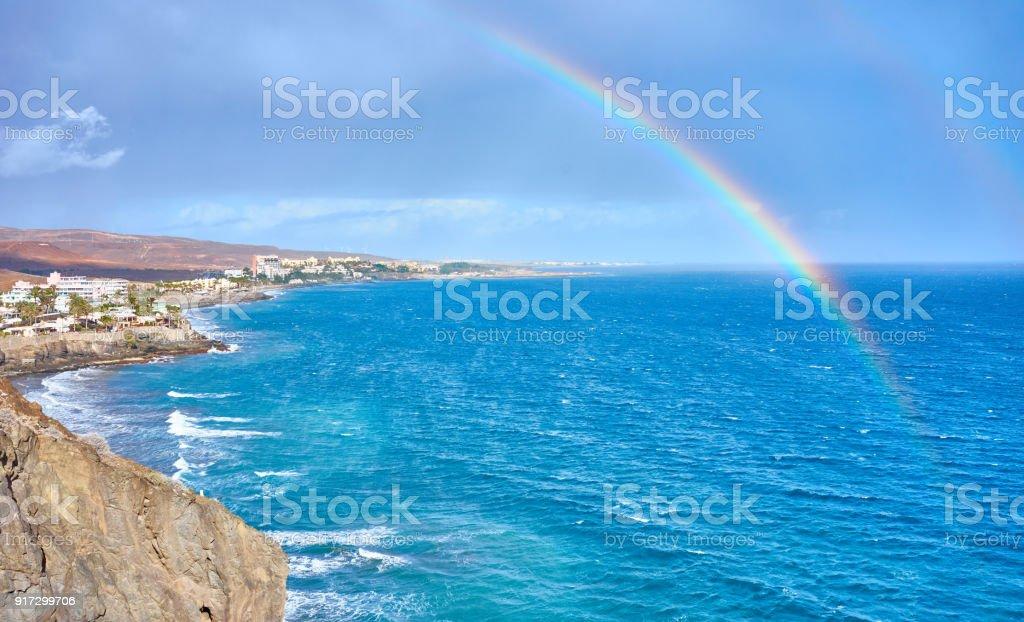 Dramatic sky with rainbow over ocean stock photo