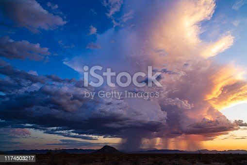 Dramatic sky with colorful storm clouds and rain falling at sunset near Salome, Arizona.