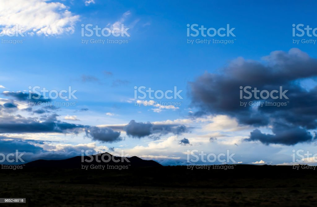 Dramatic skyscape over silhouette of mountains and flatland with stormclouds forming in very blue sky near dusk zbiór zdjęć royalty-free