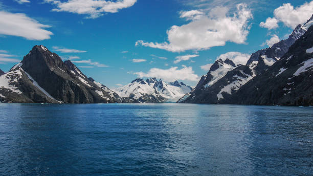 Dramatic snow covered mountainous landscape of Drygalski Fjord in southeastern South Georgia Island in the South Atlantic Ocean. Steep snow capped mountains with jagged peaks beside glacial bay on sunny day. On Antarctica cruise in the southern hemisphere. south georgia island stock pictures, royalty-free photos & images
