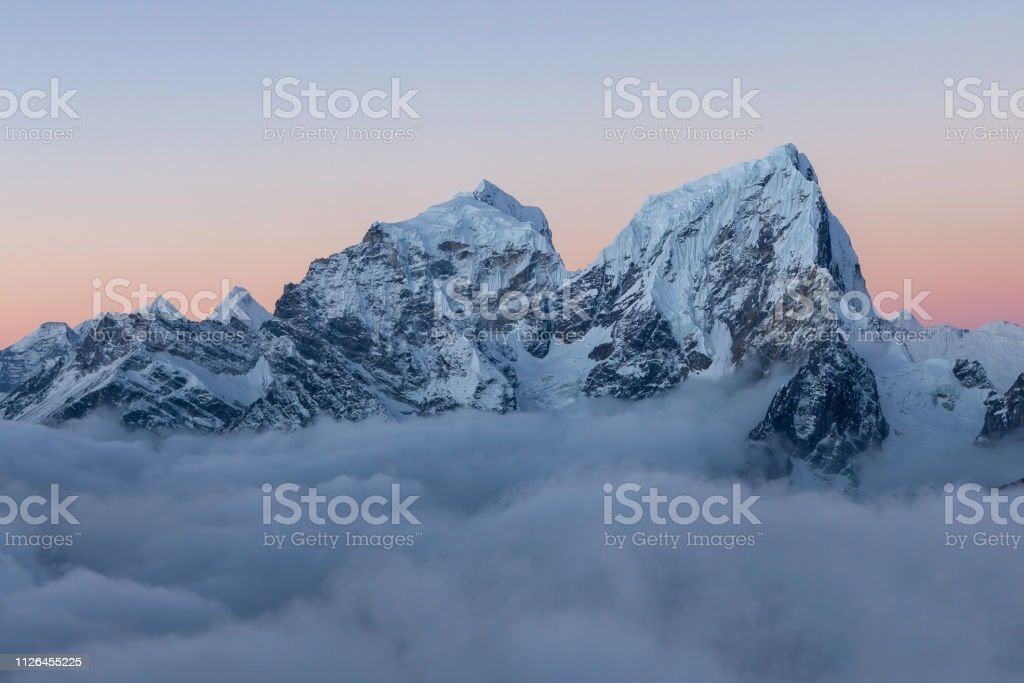 Dramatic snowy peak of mount Cholatse rising above field of clouds....
