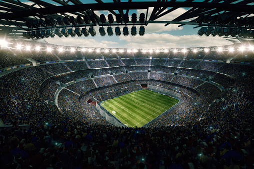 View from the upper tribunes to the soccer stadium full of spectators and lenseflares.
