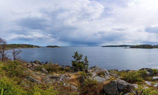 Dramatic spring weather with sun and dark rain clouds over the sea in Karlshamn, Sweden. Panoramic view.